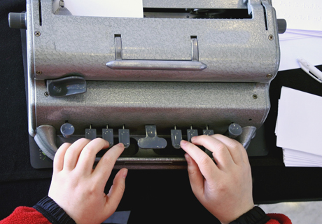 A young child learns to use a Braille typewriter.